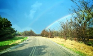 What I like about this picture is how the road curves to the left, while the rainbow veers off to the right. If you look closely you can see not only a faint double rainbow but tire tracks that appear to be following the rainbow.